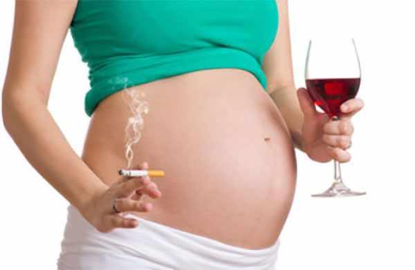 Беременная женщина с сигаретой и бокалом вина