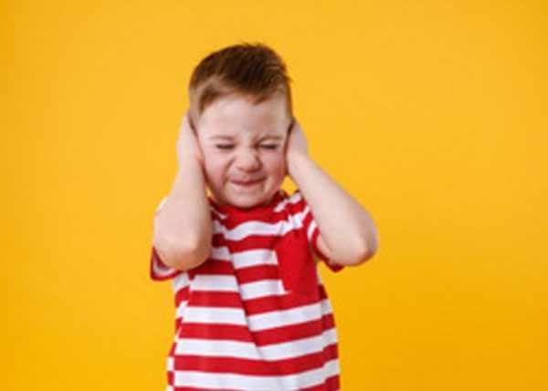 Мальчик жмет ладошами уши, испытывает боль
