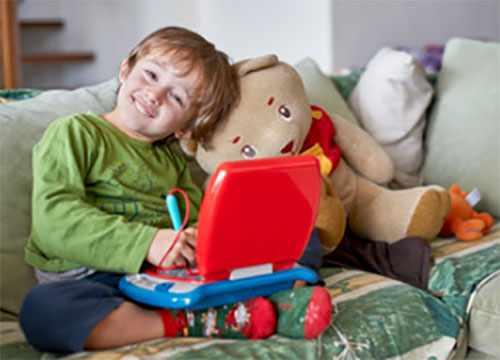 Ребенок улыбается. Сидит на диване и занимается на детском ноутбуке, рядом плюшевый медведь