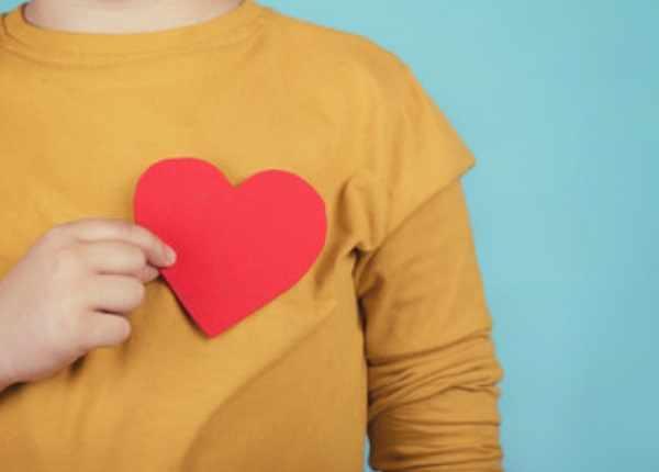 Ребенок держит возле груди картонное сердце