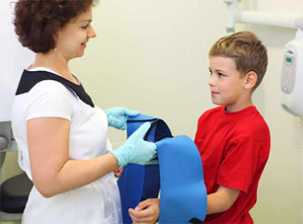 Доктор надевает мальчику свинцовый фартук
