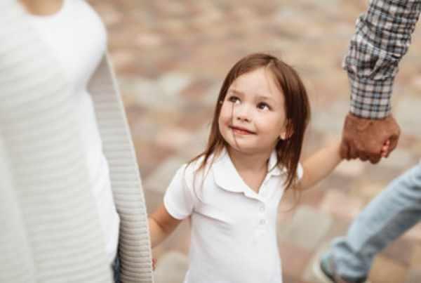 Счастливая девочка на прогулке с родителями