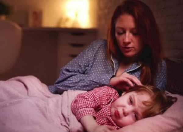 Малыш старше года плачет в кроватке. Рядом лежит мама