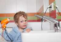 Ребенок сушит волосы