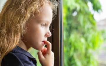 Девочка грызет ногти у окна