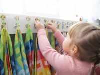 Ребенок вешает полотенце