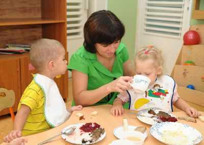 Воспитатель учит малышей этикету