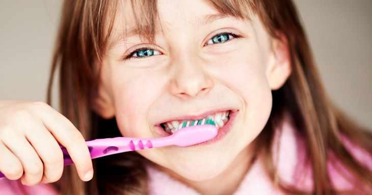 Девочка чистит зубы и улыбается