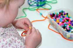 Ребенок плетет бусы