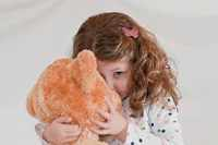Девочка прячется за мишку