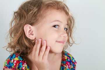 Девочка показывает сережку в ухе