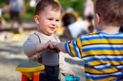 Ребенок делится игрушкой в песочнице