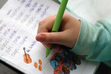 Ребенок держит в руке ручку