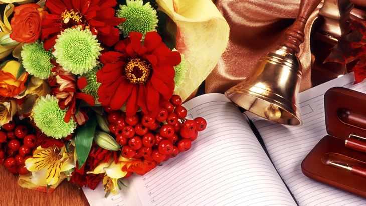 Цветы красные на столе с колокольчиком